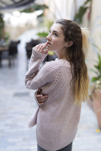 Young woman thoughtful and without looking at camera. Vertical shot with natural light. 16 Years Woman Beautiful Woman Caucasian Ethnicity Fashion Focus On Foreground Model One Person person Portrait Real People Teen Teenager Teenager Girl Warm Clothing Woman Portrait Young Women