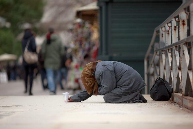 Side view of female beggar begging on footpath in city