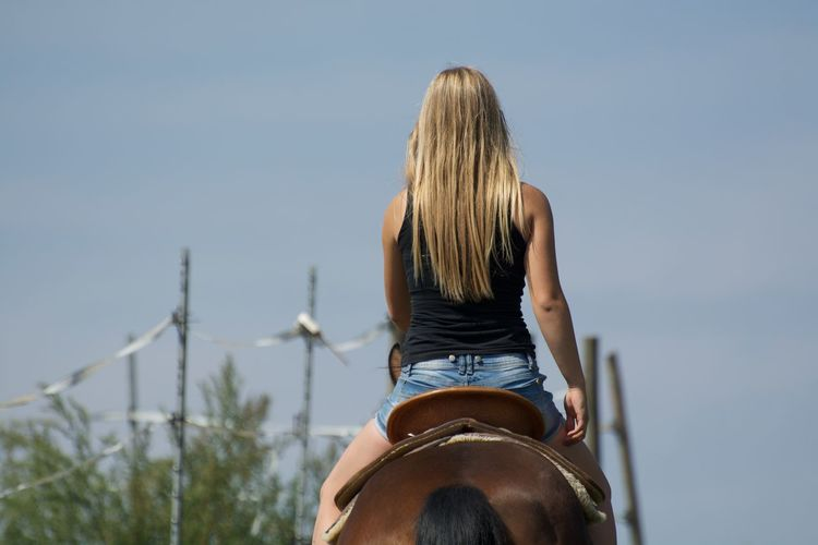 Rear view of woman riding horse against sky