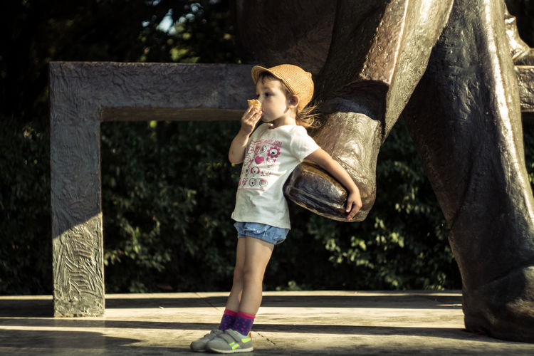 Architectural Column Casual Clothing Child Childhood Day Females Girls Hairstyle Innocence Leisure Activity Lifestyles Nature One Person Outdoors Real People Shorts Sunlight Tree