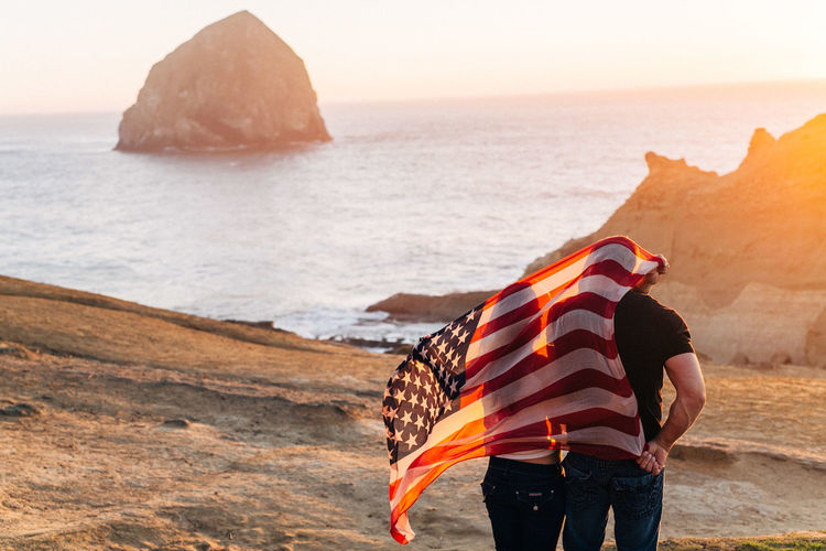 Rear view of man and woman with american flag standing at beach against sky
