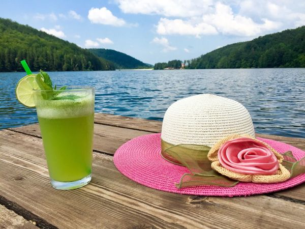 Mint lemonade glass and summer pink hat near the lake Hat Drink Outdoors Sun Hat Water Summer Drinking Glass Nature Sky Food And Drink No People Cloud - Sky Drinking Straw Beauty In Nature Mountain Close-up Freshness Pontoon Deck Wooden Lake Water Forest Lemonade