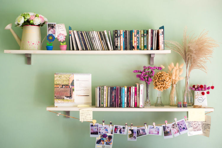 Various objects on shelves on green wall