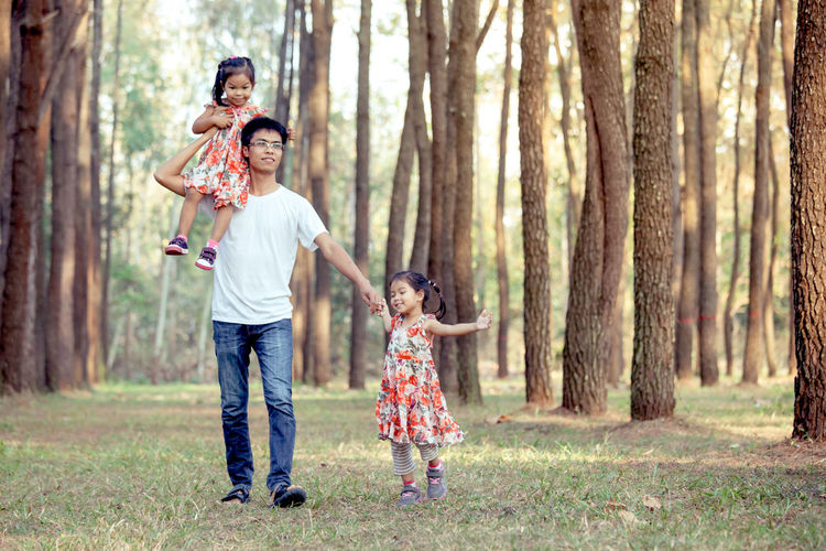 Father walking with daughters in forest