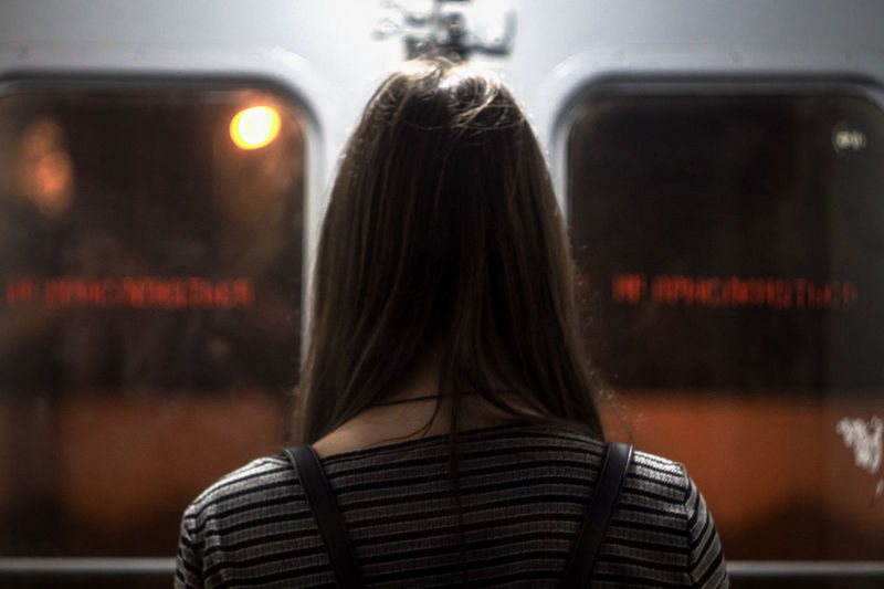 Rear view of woman standing against train