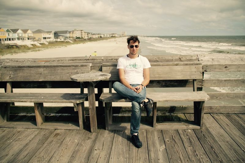 Man Ocean View South Carolina Summertime Surfside Beach Vacation Time Vacations America Bench Casual Clothing Front View Full Length Leisure Activity Lifestyles Ocean One Person Outdoors Portrait Real People Sea Seat Sitting Summer Young Adult Young Men