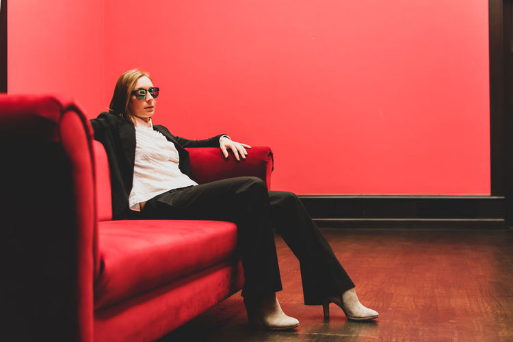Woman wearing sunglasses while sitting on sofa