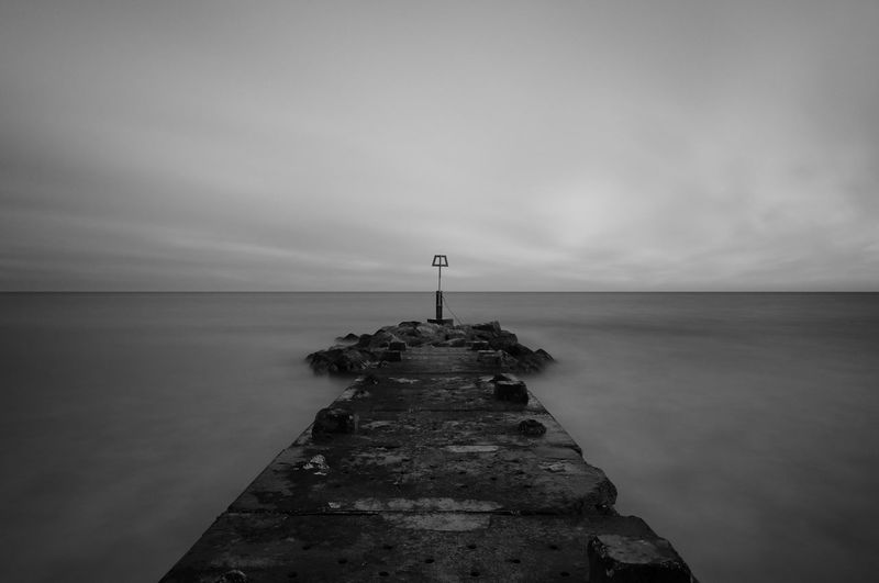 Pier over sea against cloudy sky during sunset