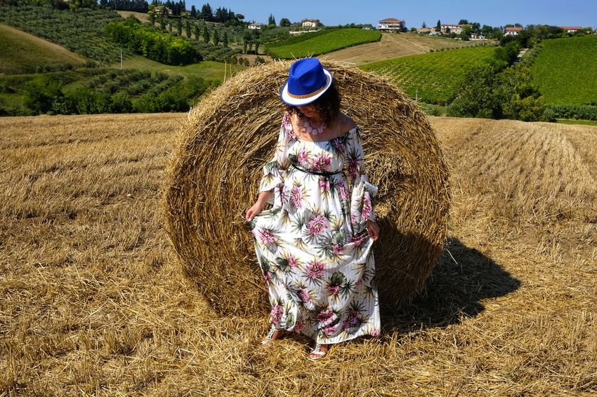 beautiful woman between round bales Woman Agriculture Beauty In Nature Clothing Day Farm Field Full Length Growth Hat Hay Land Landscape Leisure Activity Lifestyles Nature One Person Outdoors Plant Real People Round Bale Rural Scene Sunlight