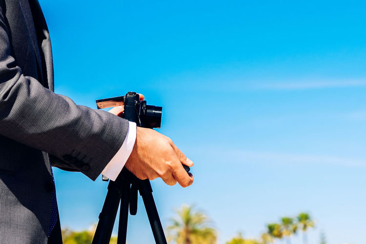 Midsection of man photographing while standing against blue sky