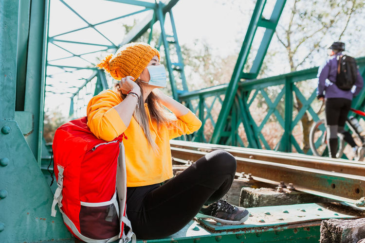 Woman wearing mask sitting on railway bridge