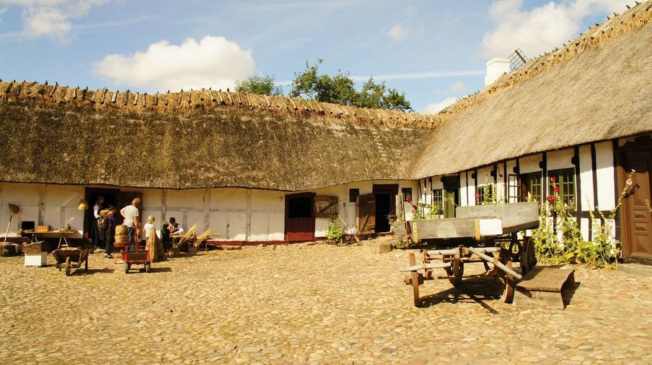 """Farm at """"Den Fynske Landsby"""" in Odense, Denmark Architecture Building Exterior Built Structure Cloud Cloud - Sky Country Life Courtyard  Day Den Fynske Landsby Denmark Farm Farm Life Group Of People Historical Building Leisure Activity Life, Lifestyles Men Open Air Museum Sitting Sunlight Water"""