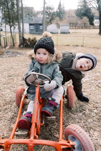 Portrait of happy man riding boy sitting outdoors