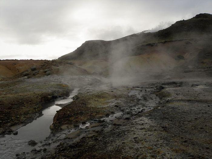 Hot spring on landscape against sky