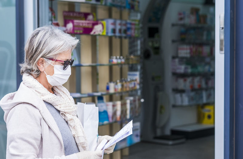 Senior woman wearing mask with prescription standing outside pharmacy