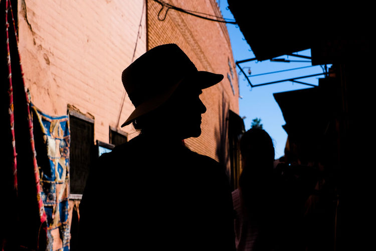 Side view of silhouette person standing against buildings and blue sky