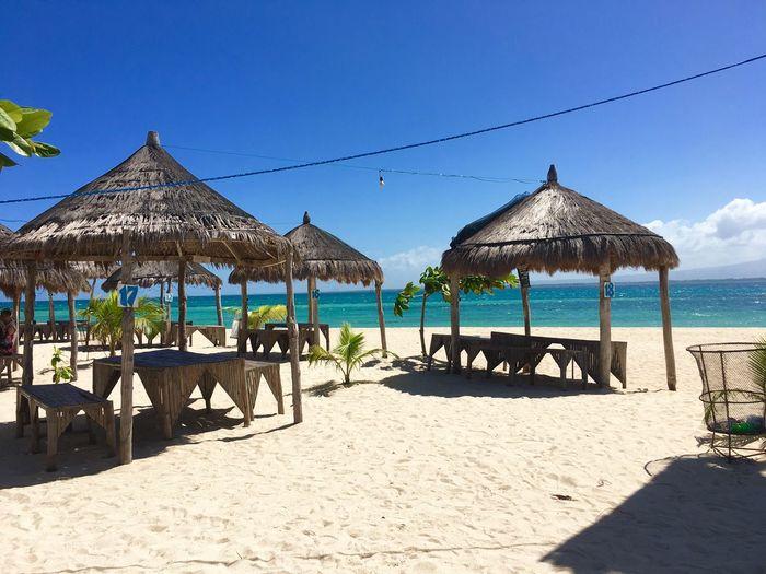 Gazebo at beach against blue sky