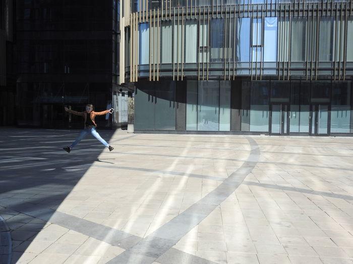 Full length of girl jumping on street in modern city