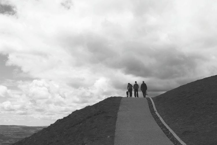 People walking on mountain against cloudy sky