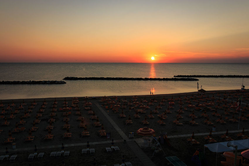 Sunrise on the beach of Torre Pedrera at Rimini in Italy Sky Sea Water Sunset Scenics - Nature Beauty In Nature Architecture Nature Beach Horizon Horizon Over Water High Angle View Sun Group Of People Orange Color Land Built Structure Real People Tranquility Outdoors Holiday Sunrise Torre Pedrera Beach Lounger