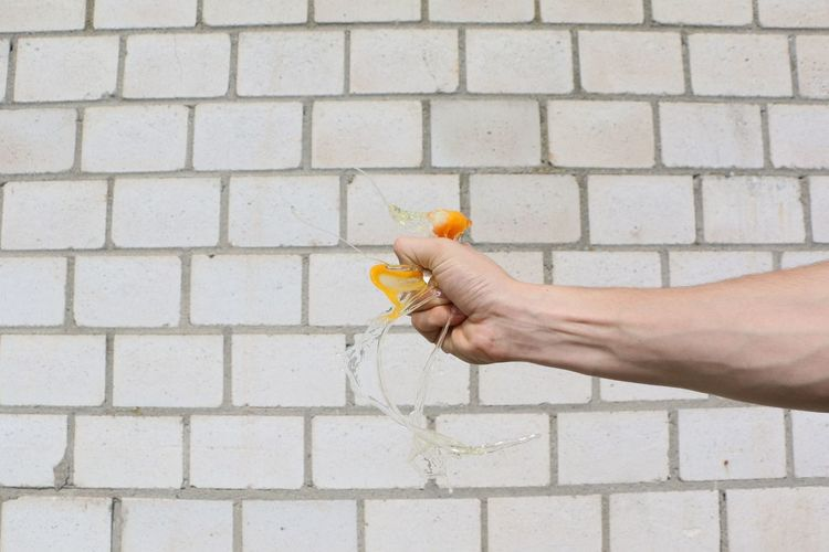Cropped Hand Of Man Breaking Egg Against Brick Wall