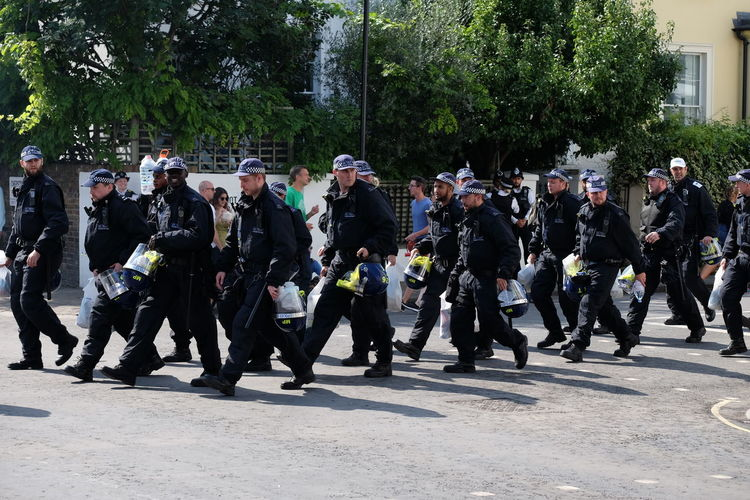 One of Many Police Squads at Nottinghill Carnival Composition GB London Uniform Hats Black Uniforms Full Frame Full Length Helmets Large Group Of People Marching Men No Incidental People Nottinghill Carnival 2017 Outdoor Photography Police Helmet Police Uniforms Policemen Real People Riot Squad Street Sunlight And Shadows Trees And Sky Uk Walking