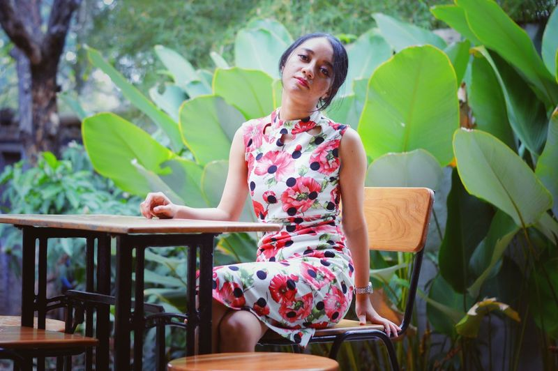 Young woman sitting on chair against plants