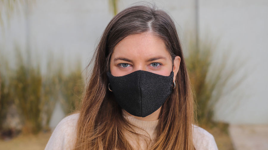 Portrait of beautiful young woman covering face