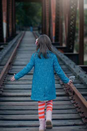 Rear view of girl walking on railroad tracks