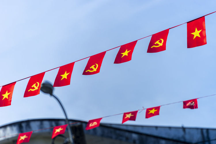 Low angle view of flags sign against sky