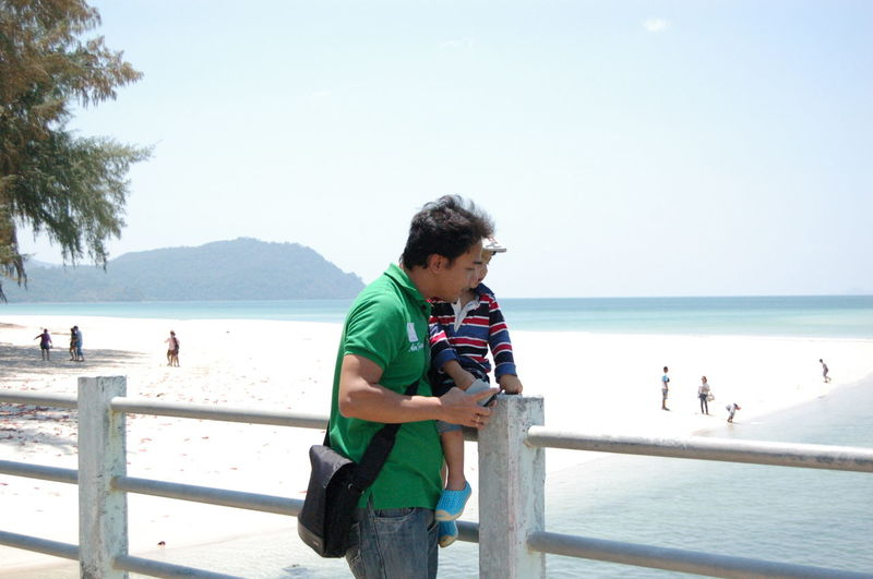 Father with son standing against sea