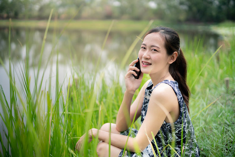 One Person Smiling Plant Young Adult Happiness Leisure Activity Holding Field Grass Technology Beautiful Woman Young Women Land Women Adult Talking Real People Looking Away Telephone Using Phone Wireless Technology Hairstyle Outdoors