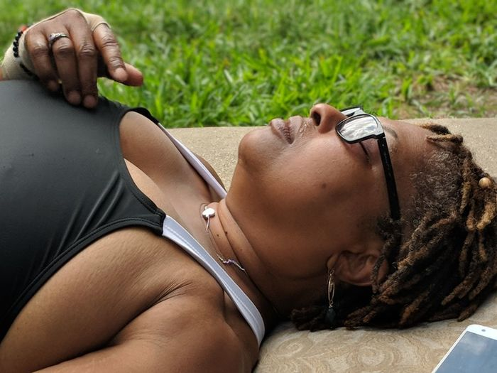 High Angle View Of Mature Woman Wearing Eyeglasses While Lying Down On Exercise Mat At Park