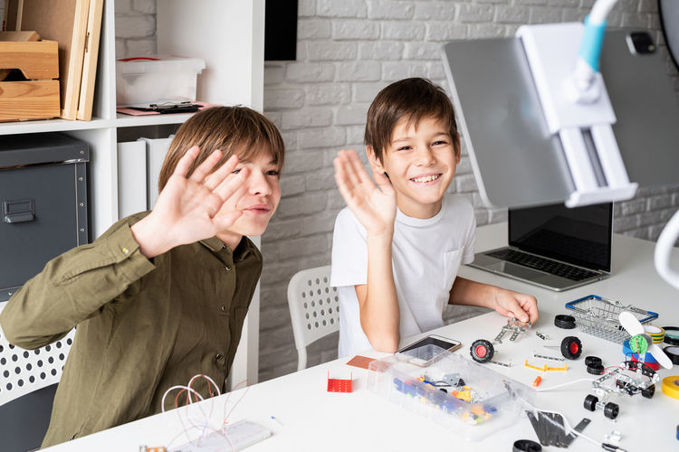 Young boys having fun making robot cars having online class on digital tablet greeting teacher