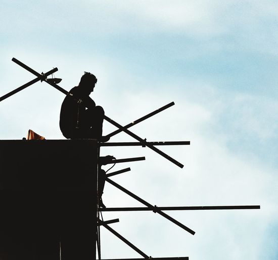 Man in silhouette siting on top of scaffolding