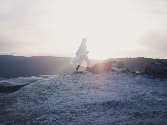 Woman In White Clothes Walking In Sunlight In Snowcapped Mountains