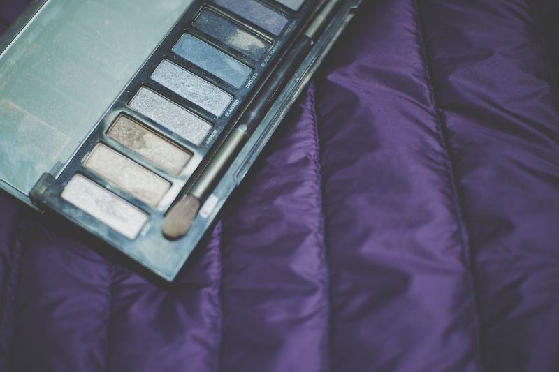 High angle view of eyeshadow on bed