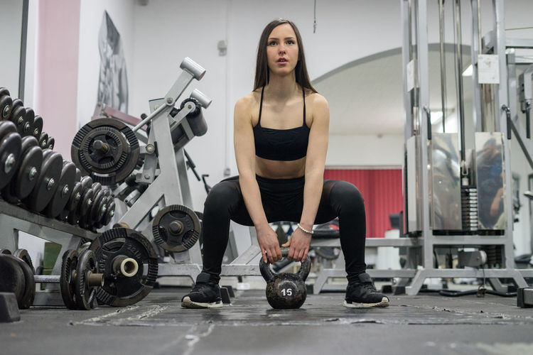 Full Length Of Young Woman Lifting Kettlebell At Gym