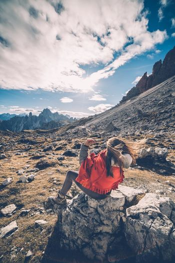 Rear View Of Woman Sitting On Cliff Against Cloudy Sky