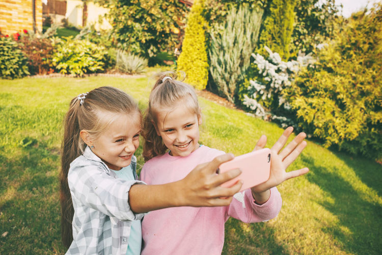 Cute girls taking selfie while standing outdoors