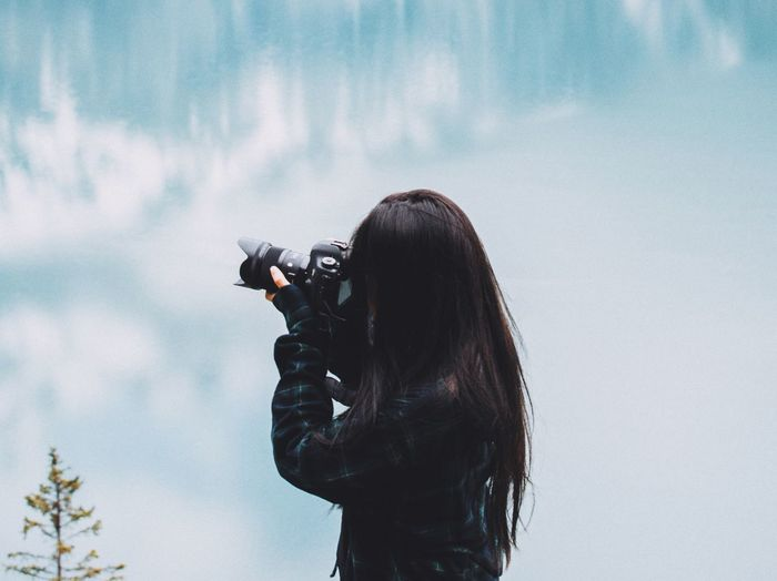 High angle view of woman photographing with digital camera against cloudy sky