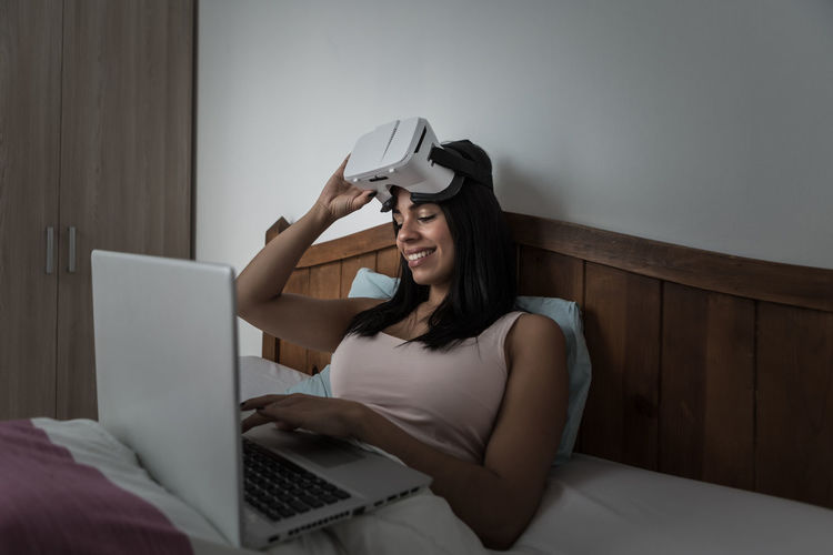 Young woman using phone while sitting on bed at home