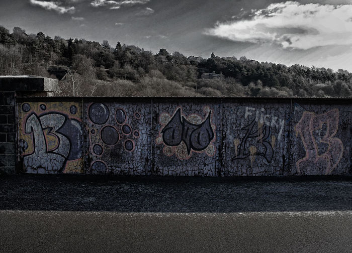 Graffiti on wall by road against sky