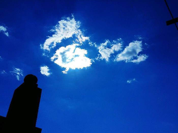 Low angle view of silhouette man against blue sky