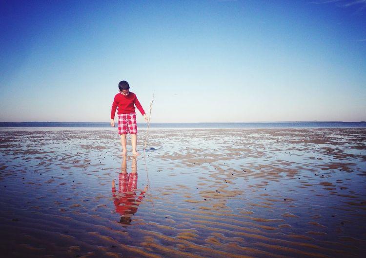 Boy walking at beach against clear blue sky