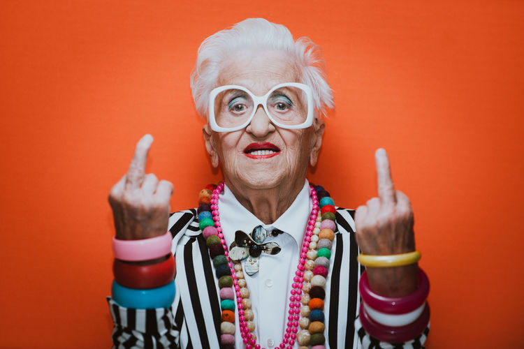 Portrait of stylish senior woman wearing colorful jewelry showing middle finger against red background