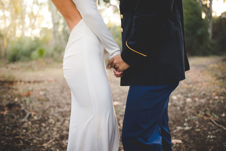 Midsection Of Bride And Groom Holding Hands And Standing On Field