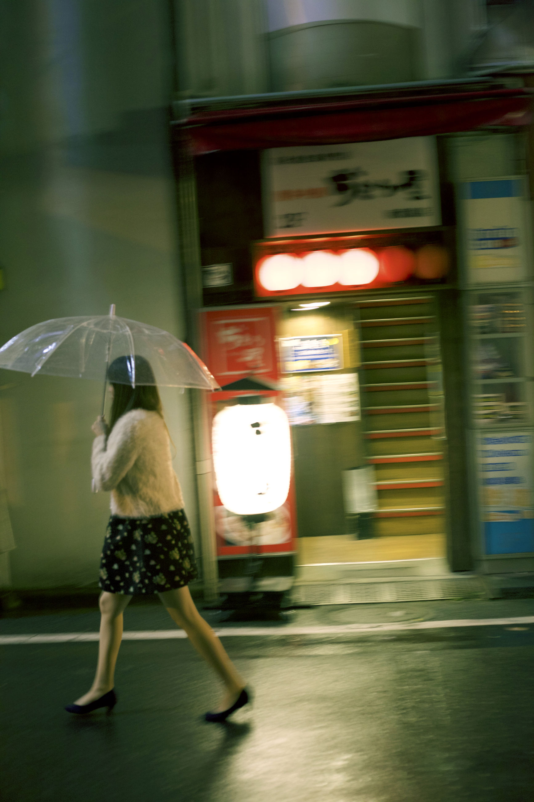 blurred motion, motion, real people, one person, full length, umbrella, women, illuminated, transportation, protection, adult, city, lifestyles, architecture, mode of transportation, speed, casual clothing, public transportation, rain, outdoors, rainy season