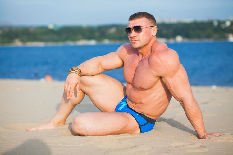 Shirtless bodybuilder while standing on beach against bay of water