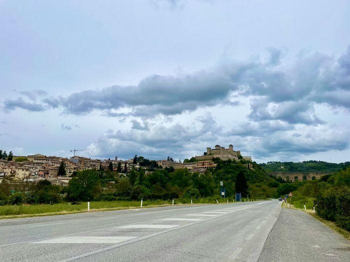Road by buildings against sky in city